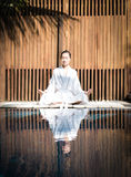 Asian Lady practicing Yoga. On the wooden desk stock images
