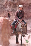 Asian lady riding donkey in Petra Jordan Royalty Free Stock Images