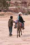 Asian lady riding donkey in Petra Jordan Stock Image