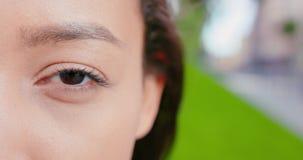 Asian lady's eye blinking outdoors.  stock video
