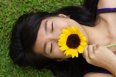 Asian lady smelling flower. On  her back on grass with closed eyes Royalty Free Stock Images