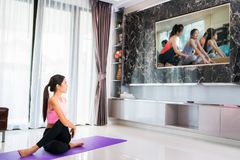 Asian lady start to training Yoga by follow coach in television. In living room, in luxury mome Royalty Free Stock Photo