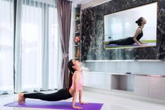 Asian lady start to training Yoga by follow coach in television. In living room, in luxury mome Royalty Free Stock Photos