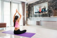 Asian lady start to training Yoga by follow coach in television in living room. In luxury mome Stock Photos