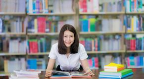 Asian lady student read a book in campus library in Universit stock photos