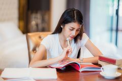 Asian lady student read a text book for prepare to examination o. N the bedroom, this immage can use for education, reading, homework and relax concept royalty free stock images