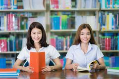 Asian lady student study and do home work in library in University royalty free stock photos