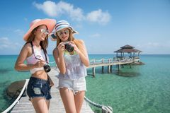 Asian lady travel resort in Kood island togather. And take photo in wooded bridge to harbor, This immage can use for travel, resort, beach, summer and holiday royalty free stock image