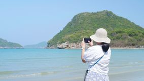 Asian lady try to take a picture at the beautiful sea and beach. Island at BG. Asian lady try to take a picture at the beautiful sea and beach. Island at stock video