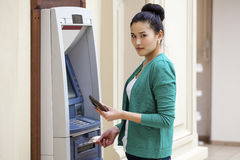 Asian lady using an automated teller machine Royalty Free Stock Photography