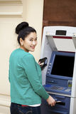Asian lady using an automated teller machine Stock Photography