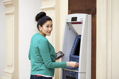 Asian lady using an automated teller machine Royalty Free Stock Image