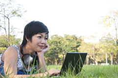 Asian lady using computer in a field Royalty Free Stock Image