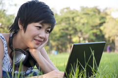 Asian lady using computer in a field Royalty Free Stock Photos