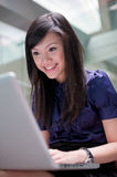 Asian lady using laptop on location. Asian lady at work while on the go, smiling at the screen of the laptop Royalty Free Stock Photos