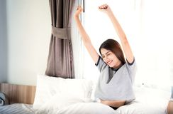 Asian lady in wake up action in the bed room stock photo