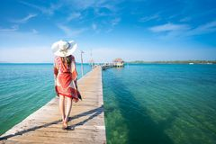 Asian lady walk in wooded bridge to harbor in Koh Mak. Mak and Kood island is travel place in Thailand, This image can use for Holiday, summer, beach, sea and stock images