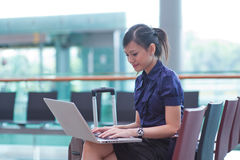 Asian lady working on her laptop. At the airport Royalty Free Stock Photo