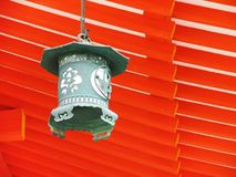 Asian Lantern. A hanging Japanese lantern beneath a bright orange wooden roof Stock Photos