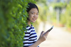 Asian leaning green leaves with computer tablet in hand smiling Royalty Free Stock Photos