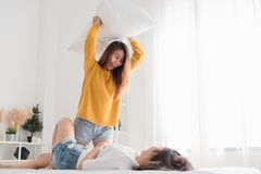 Asian lesbain woman playing pillow flight together on bed in whi royalty free stock image