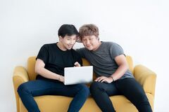 Free Asian LGBT Gay Couple Using  Laptop Computer Together In The Living Room At Home Royalty Free Stock Image - 195807216