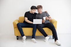 Free Asian LGBT Gay Couple Using  Laptop Computer Together In The Living Room At Home For Work Royalty Free Stock Images - 195803619