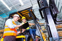 Asian lift truck driver and foreman in storage. Asian fork lift truck driver discussing checklist with foreman in warehouse Royalty Free Stock Photos