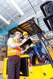 Asian lift truck driver and foreman in storage Royalty Free Stock Images