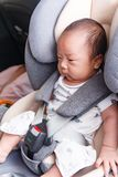 Asian little baby fastened with security belt in safety car seat. Little baby child fastened with security belt in safety car seat royalty free stock photos