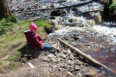 Little girl sitting near a mountain river. royalty free stock photo