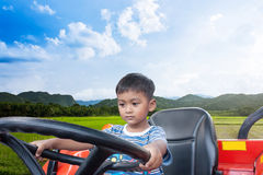 Asian little boy driver tractor on rice field Stock Image