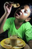 Asian Little boy eating biscuit with a glass of tea.