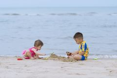 Asian little boy and his baby sister playing together on the sandy beach. Brethren playing together on the beach on sea background stock image