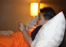 Asian Little boy playing game. In bed Stock Images