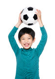Asian little boy raise soccer ball up Royalty Free Stock Image