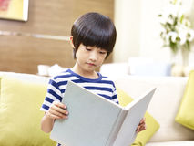 Asian little boy reading book at home Stock Photography