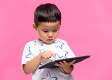 Asian little boy using dgital tablet. Asian young little boy royalty free stock images
