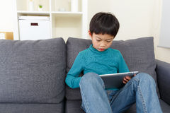 Asian little boy watching on tablet and sitting on sofa royalty free stock images