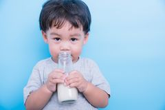 Asian little child boy about 2 year drinking milk from bottle glass itself. On blue background royalty free stock image