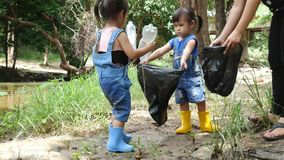 Asian little child with family picking up garbage and plastic bottle in black bags on the edge of a public river. Environmental protection concept stock video footage