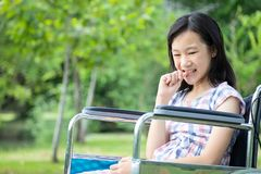 Free Asian Little Child Girl Feeling Stressed,worried Female Bites Finger Nails In Wheelchair Outdoor Park,girl Patient With Nervous Stock Photo - 155738760