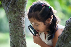 Asian little child girl looking through a magnifying glass Stock Image
