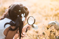 Asian little child girl looking through a magnifying glass Royalty Free Stock Image