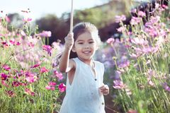 Asian little child girl running and having fun in the garden. Happy asian little child girl running and having fun in the cosmos flower field in vintage color Stock Image