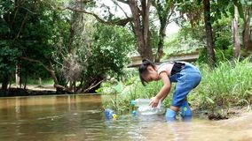 Asian little child is picking up plastic garbage floating on the bank of the river. Environmental protection concept.