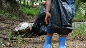 Asian little children is picking up garbage and plastic bottle in black bags on the edge of a public river. Environmental protection concept stock video