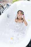 Asian little Chinese girl blowing bubbles. In bathtub at home stock photo