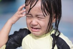 Asian Little Chinese Girl crying in Swimming Pool Stock Image
