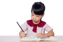 Asian Little Chinese girl drawing with color pencils. In isolated white background royalty free stock image